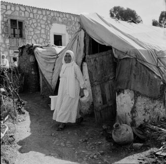 A Palestinian refugee woman in front of her shelter (early 1950s ) at Ein el-Hilweh camp for Palestine refugees. Credit:UNRWA